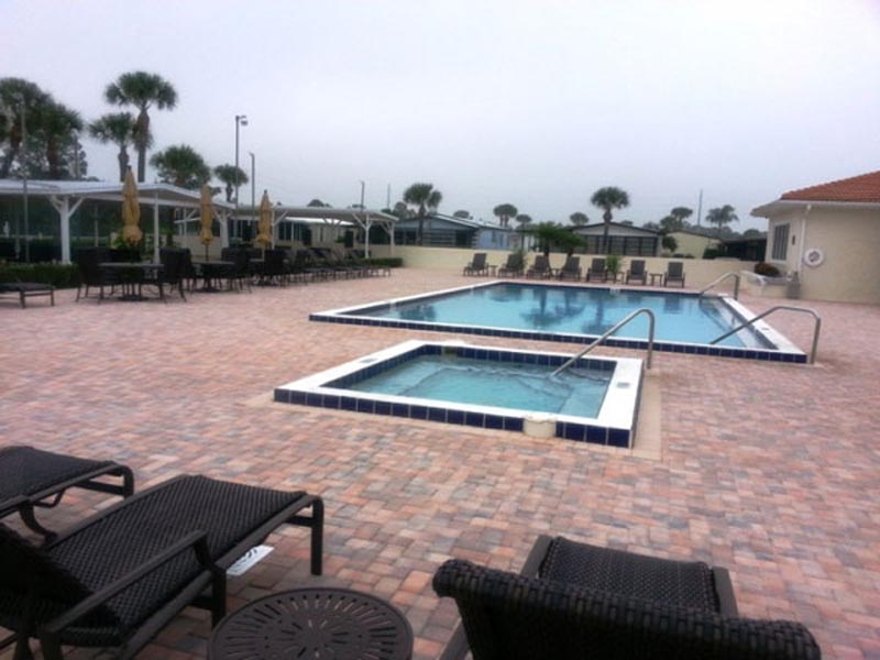 Pool and spa surrounded by brick patio and lounge chairs.